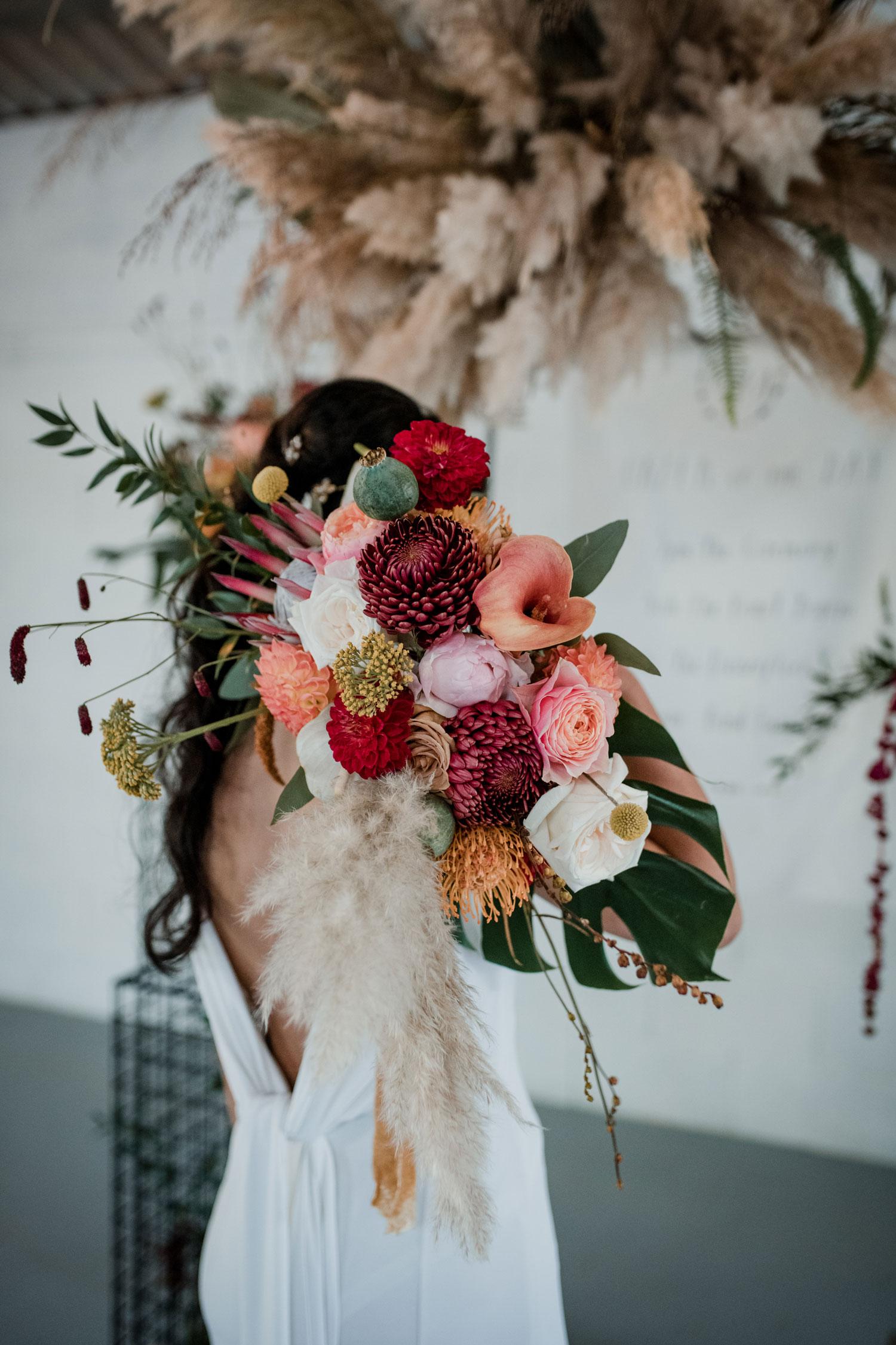 bride holding bridal bouquet protea monstera cheese leaf pampas grass cloud wedding florist london