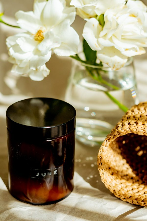 June vegan soy scented candle with flowers in a vase