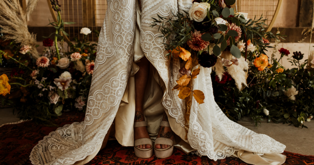 Brides legs and shoes in front of ceremony area flowers holding bouquet iris co