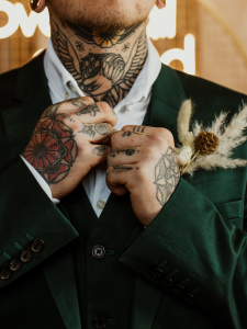 groom in dark green suit and tattoos with pampas grass and dried flower buttonhole