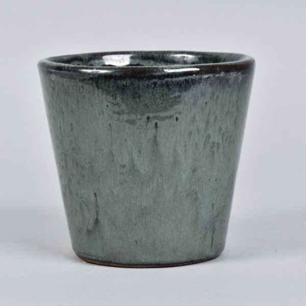 teal painted ceramic plant pot one a white background